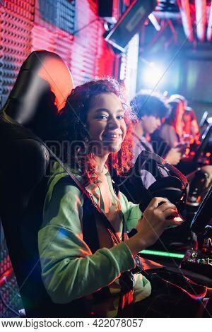 Cheerful Africam American Girl In Car Simulator Smiling At Camera Near Blurred Friends.