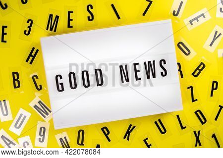 Lightbox With Message Good News On Yellow Background With Black Letters Randomly Scattered. Concept