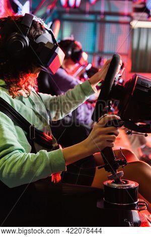African American Teenage Girl Racing On Car Simulator Near Blurred Boy.