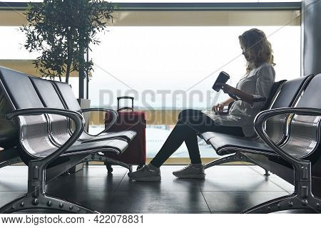 Young Woman Tourist With Suitcases Sits In The Waiting Room Of The Airport And Is Waiting For The Fl