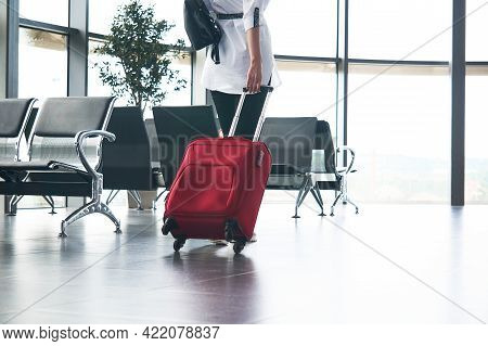 Woman Traveler With Luggage Climbs The Stairs In Airport Or Train Station Lounge; Legs And Suitcase