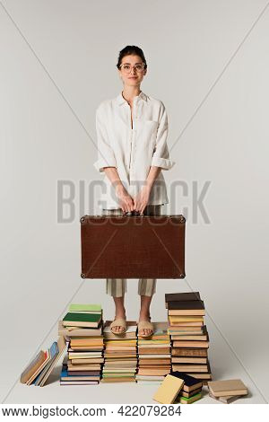Full Length Of Pleased Young Woman In Glasses Holding Suitcase While Standing On Pile Of Books Isola