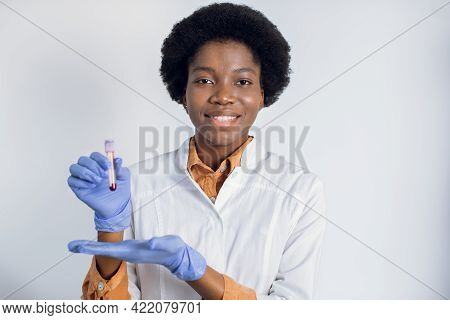 Portrait Of Pretty Female African American Laboratory Assistant, Wearing White Coat And Blue Gloves,
