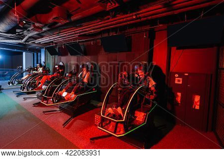 Teenage Friends In Virtual Reality Headsets Gaming On Racing Simulators.