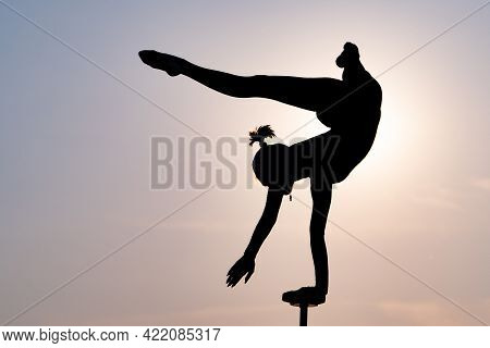 Silhouette Of Flexible Acrobat Doing Handstand On The Dramatic Sunset Background. Concept Of Individ