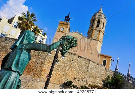 SITGES, SPAIN - MARCH 3: Facade of Church of Sant Bartomeu i Santa Tecla on March 3, 2012 in Sitges, Spain. The 17th century church next to the sea is an iconic building of the gay-friendly city