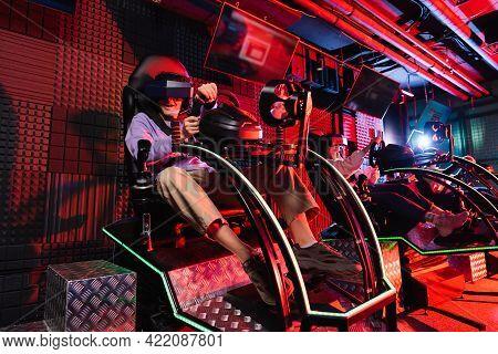 Teenage Friends Gaming In Car Racing Simulators In Vr Play Zone.