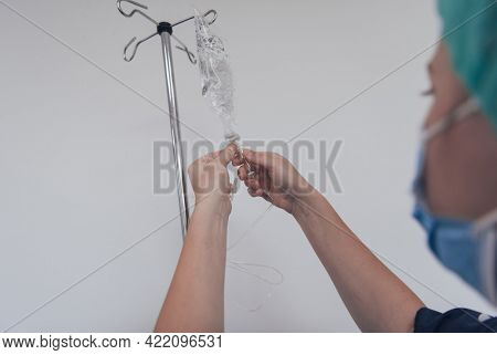 General practitioner holding intravenous drip infusion. Doctor handling IV fluid drip with copy space on white background. Nurse performing Intravenous therapy.