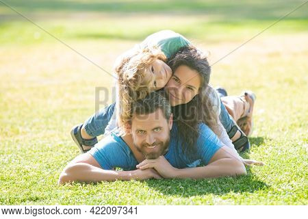 Family Hugging And Embracing, Lying On Grass In Park. Portrait Of A Happy Smiling Family Relaxing In