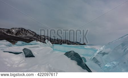 Blocks Of Ice Hummocks On A Frozen And Snowy Lake. Turquoise Shiny Ice Floes Close-up. Mountain Rang