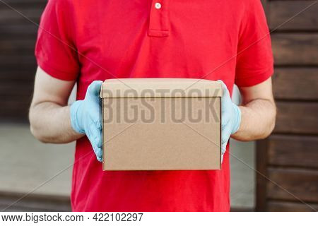 Close Up Of Delivery Man In Red Uniform Hold Cardboard Box. Service In Quarantine.