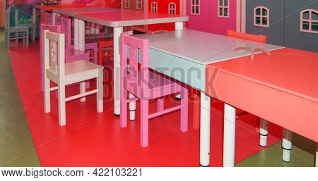 A Set Of Cute Childrens Tables And High Chairs In The Kindergarten Playroom.