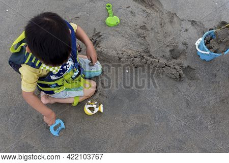 Child Digs Holes With Toys In Sands On The Beach. One Little Asian Boy In Life Jacket Playing In Saf