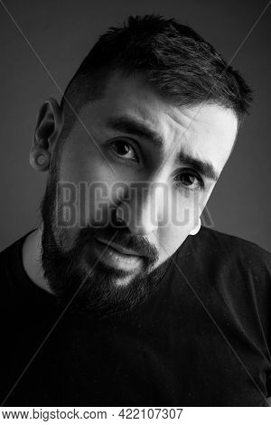 Portrait Of A Young Bearded Man On A Gray Background. The Young Man Smiles. Black And White Photo.