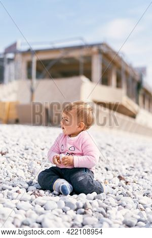 Child In A Pink Blouse And Blue Pants Sits On A Pebble Beach And Holds A Pebble In His Hand, Turning