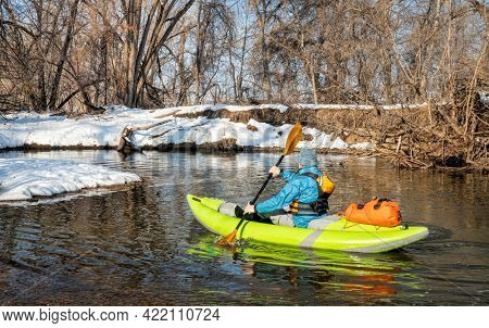 senior male paddler is paddling an inflatable whitewater kayak on a small river - Poudre River in Fort Collins, Colorado, winter or early spring scenery