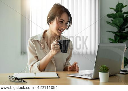 Beautiful Asian Woman Freelancer Working On Laptop With Coffee Cup In Home Office.