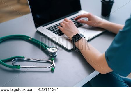 Back Close-up View Of Hands Of Unrecognizable Female Practitioner Wearing Blue Green Medical Uniform