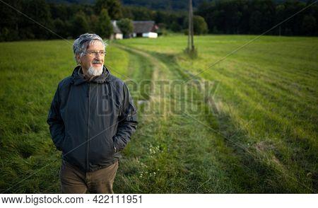 Senior man enjoying the outdoors, hiking, walking through lovely nature