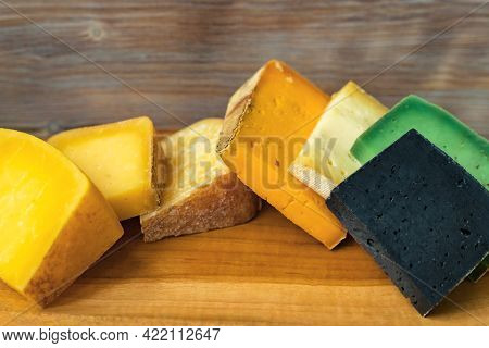 Wooden Cutting Board With Different Cheese Color Chunks On Wood Wall Background. Close Up. Selective
