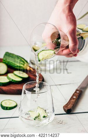 Hand With Jug Pours Infused Water With Sliced Cucumber