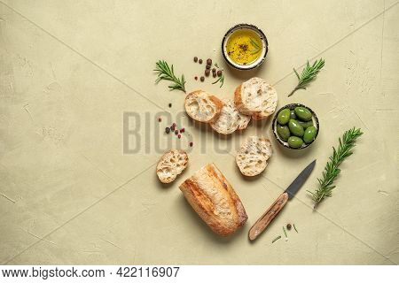 Fresh Ciabatta Bread With Olive Oil, Olives And Rosemary On A Beige Concrete Background. Italian Foo