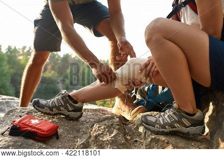 Young Caucasian Man Bandaging Injured Woman Knee With Sprain During Hiking In Summer Nature, Cropped