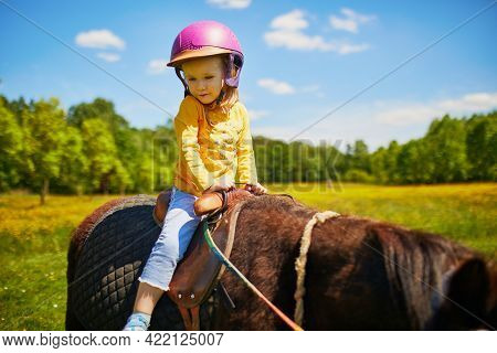 Adorable Three Years Old Girl Riding A Pony. Little Child Practicing Horseback Riding. Equestrianism
