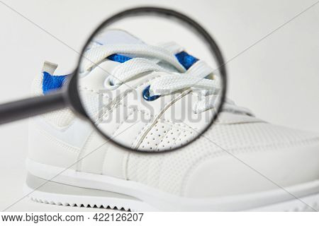 The Buyer Searches For Defects And Macro Detail In Shoes With A Magnifying Glass. Style And Fashion