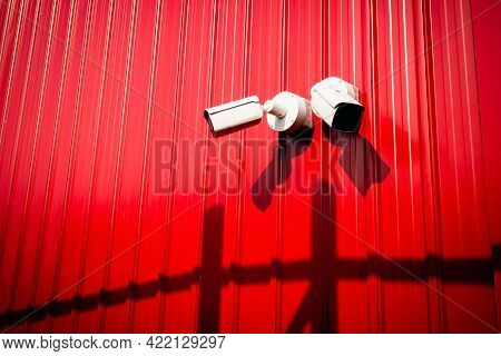 A White Cctv Camera Mounted Next To A Red Metal Wall For The Background. Installing Cctv Camera In P