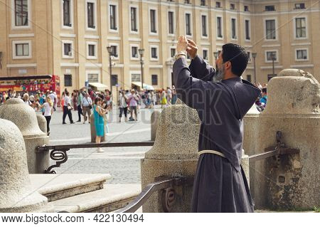Vatican, Italy, August 12, 2014 St. Peter's Square, Priest Takes Pictures On The Phone, Tourists