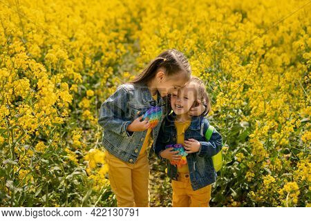 Two Girls In A Rapeseed Field Tenderly Embrace Each Other And Laugh While Holding A Popular Popit To