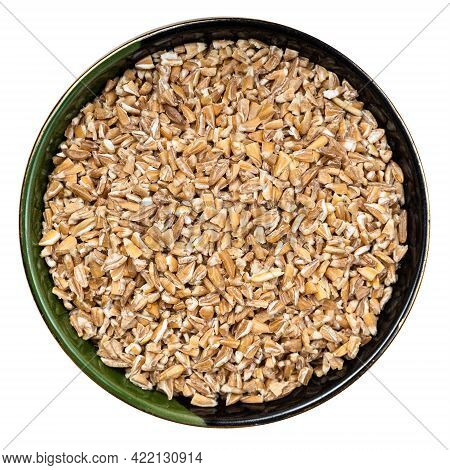 Top View Of Crushed Emmer Farro Hulled Wheat Groats In Round Bowl Isolated On White Background