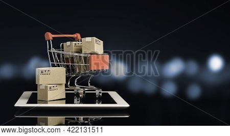 Shipping Paper Boxes Inside Red Shopping Cart Trolley On Tablet With Black And Blue Bokeh Background