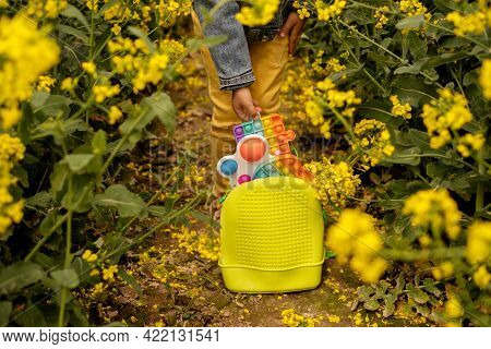 The Child Takes A Popit Toy In The Form Of A Puzzle From The Backpack. A Rucksack Full Of Plastic To