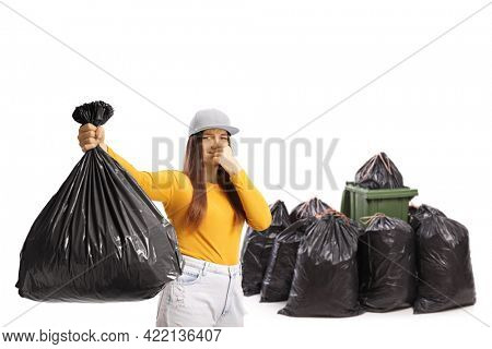 Young female holding a smelly bin bag in front of a bin and a pile of black bags isolated on white background