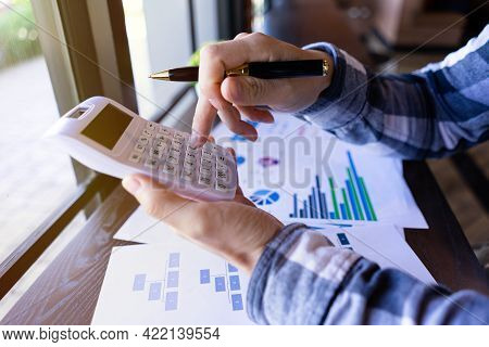 Businessman Holding Pen And Press A Calculator To Calculate Financial Report Or Company's Profit Mon