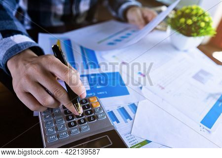 Close Up Businessman Using Calculator And Reading Paper Document About Business Data, Accountancy Do
