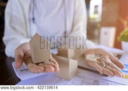 Real Estate Agent's Or Realtor Showing Small Miniature Model House And Key House. Mortgage Property