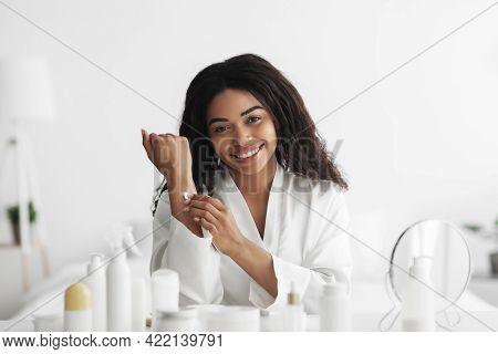 Body Nourishing Products. Pretty Black Lady In Bathrobe Applying Moisturizing Lotion Or Cream On Bod