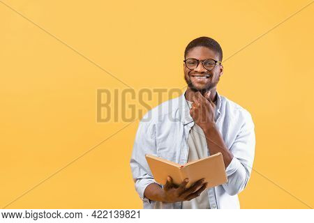 Learning Concept. Happy Young African American Guy Reading Book For Education On Yellow Background W
