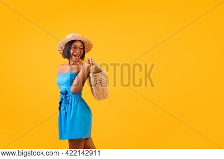 Portrait Of Gorgeous Black Lady In Summer Outfit Holding Straw Beach Bag, Looking At Free Space On O