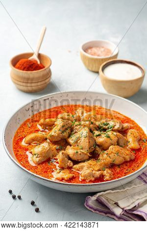 Chicken Stew With Paprika, Onion And Sour Cream In Plate On Concrete Background. Traditional Hungari