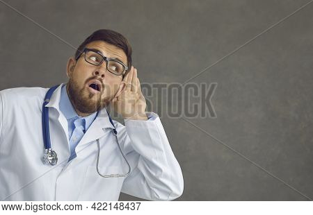 Funny Curious Doctor With Hand At Ear Listening To Colleagues Sharing Work Gossips