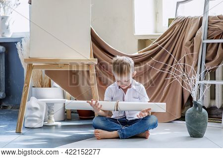 Boy In Jeans And A Shirt In The Interior Of An Old Art Workshop. The Child Is Fond Of Painting And H
