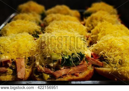 Hot Homemade Cheeseburgers Sprinkled With Grated Cheese In The Form Of Round Sandwiches On A Pan Of