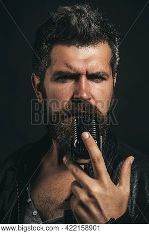 Male Vocalist Singing In Microphone In Recording Studio. Handsome Bearded Man In Leather Jacket With