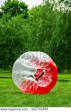Red Zorbing Balloon On The Summer Lawn. Inflatable Zorb Ball Outdoor. Leisure Activity Concept With