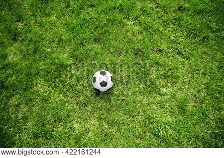 Football Soccer Ball On Green Grass Field. Top View, Copy Space