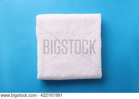 White Terry Towel Is Folded On Blue Background